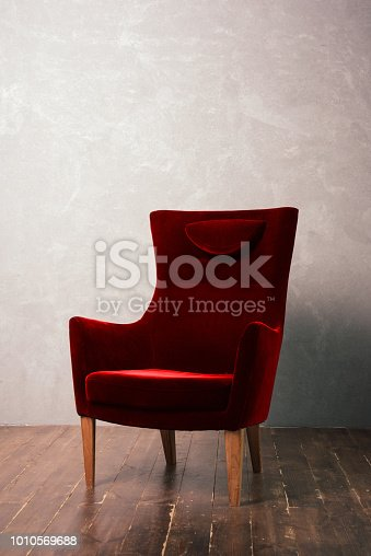 istock Luxurious red velor armchair stands near the textural wall on a dark wooden floor 1010569688