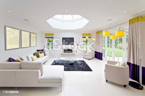 a beautifully furnished morning room in an expensive new home dressed in a modern style. A large skylight together with large patio doors allow plenty of light to illuminate the room. The colour theme is predominantly whites and creams with yellow and pruple as highlight colours. The artwork on the wall belongs to the Photographer and has a Property Release.