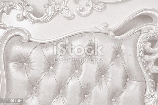 A DSLR photo of luxurious sofa detail with leather upholstery.