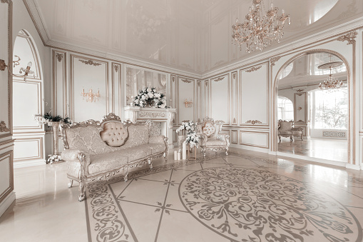 Luxurious vintage interior with fireplace in the aristocratic style. Large Windows and mirrors. Columns and arches, ornament on the glossy floor
