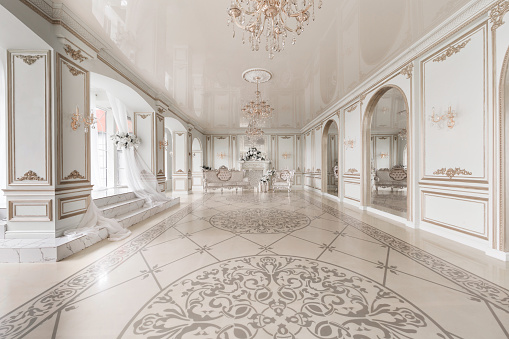 Luxurious vintage interior with fireplace in the aristocratic style. Large Windows and mirrors. Columns and arches, ornament on the glossy floor.