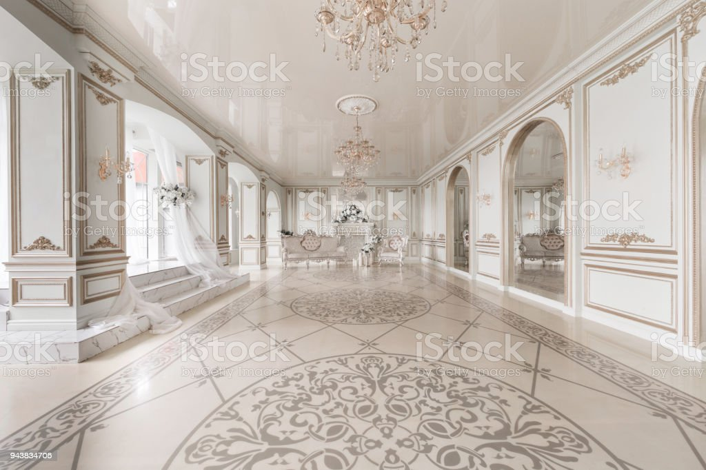 Luxurious vintage interior with fireplace in the aristocratic style. Large Windows and mirrors. Columns and arches, ornament on the glossy floor stock photo
