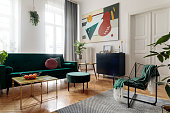 istock Luxury and modern home interior with design furniture, armchair, tables, pouf and accessroies. A lot of plants in the room. White walls with abstract image. Stylish decor of sitting room. 1125385998