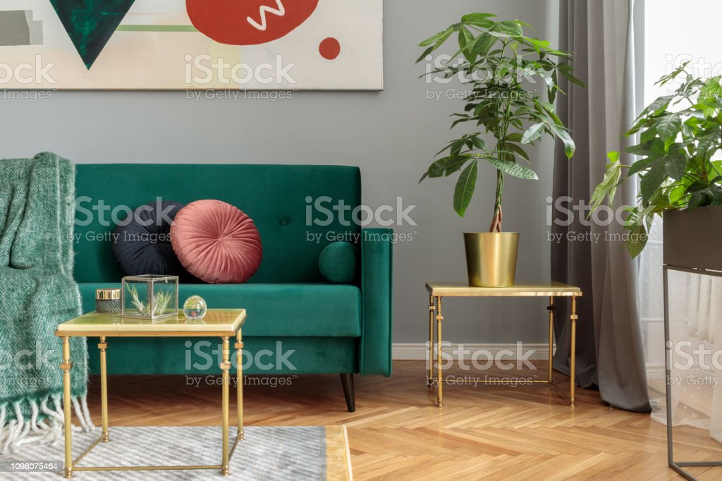 Luxury And Modern Home Interior With Green Velvet Design Sofa Coffee Tables Color Pillows Blanket Tropical Plants In Metal Stand Grey Walls With Abstract Painting Stylish Decor Of Living Room Stock Photo