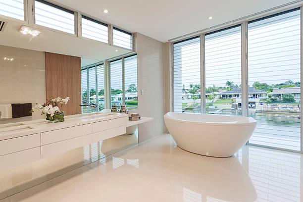 A luxury bathroom overlooking an outdoor view stock photo