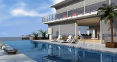 Luxury beach house reflected in the tranquil pool surrounded by sun loungers with a yacht in the background