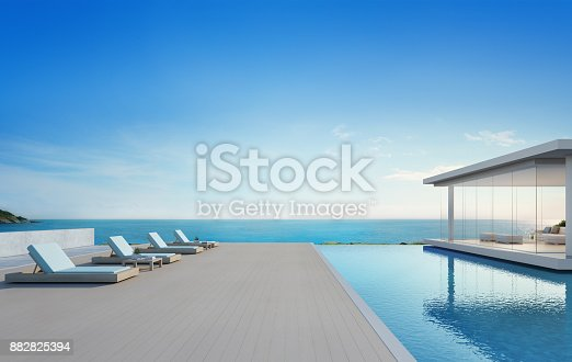 istock Luxury beach house with sea view swimming pool and terrace in modern design, Lounge chairs on wooden floor deck at vacation home or hotel - 3d illustration of contemporary holiday villa exterior 882825394