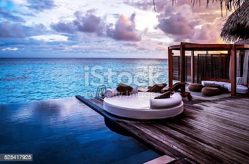 Luxury beach resort, bungalow near endless pool over sea sunset, evening on tropical island, summer vacation concept