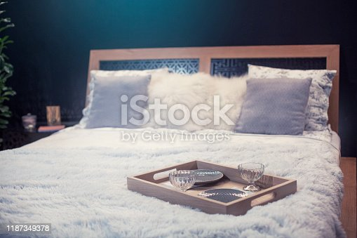 Modern double bed with beautiful light gray synthetic fur blanket and serving tray