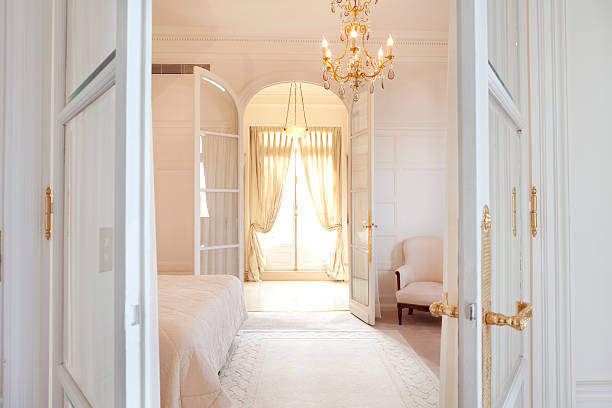Luxury Bedroom Suite in Paris All white luxurious Parisian style bedroom suite with golden accents on the chandelier and door handles.   luxury hotel room stock pictures, royalty-free photos & images