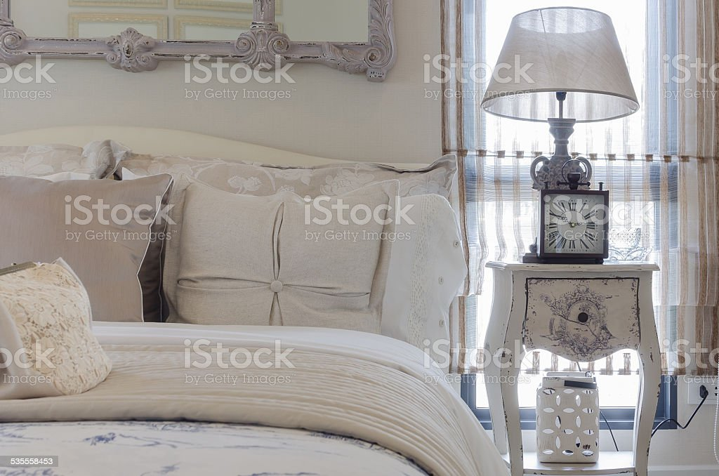 luxury bedroom with lamp and clock on white table stock photo