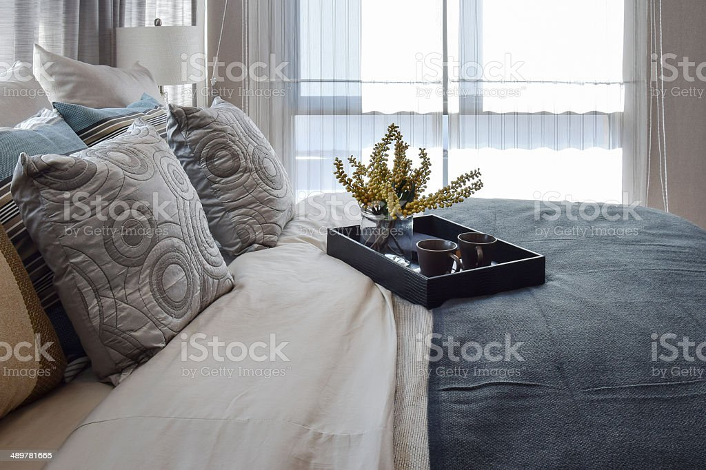 luxury bedroom with striped pillows and decorative tea set stock photo
