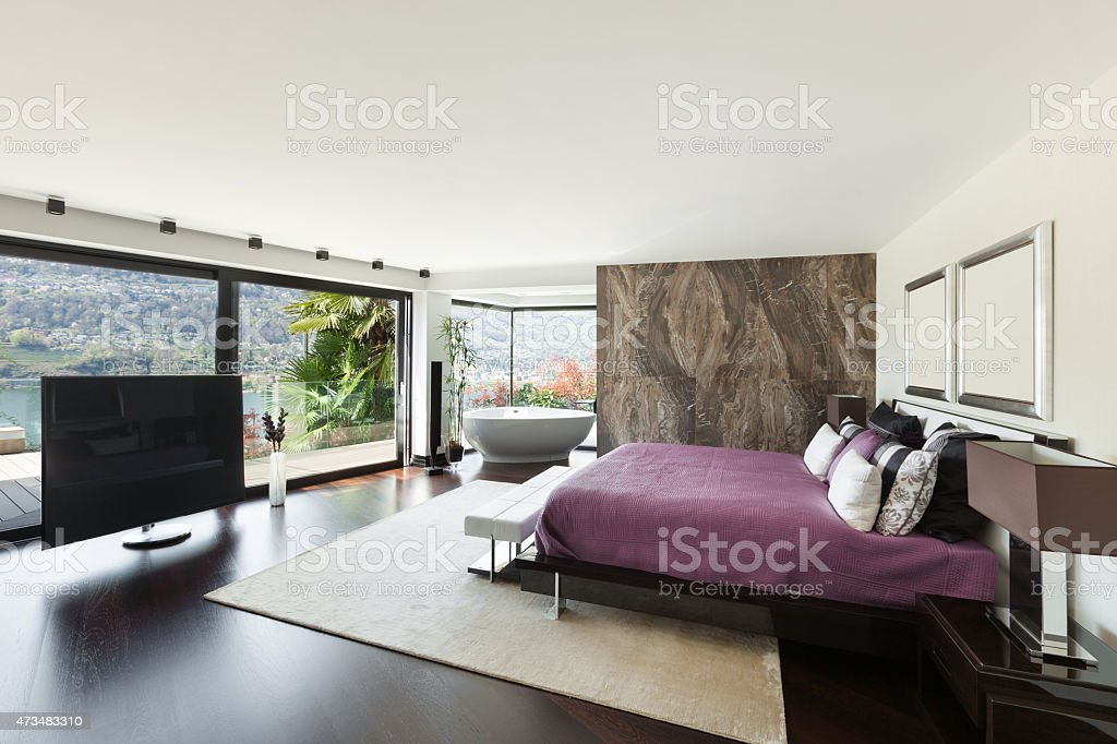 Luxury bedroom with views out of large windows stock photo