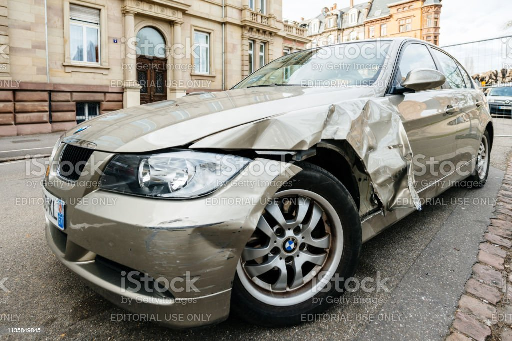 Detail of luxury BMW german car parked on city street with damaged...