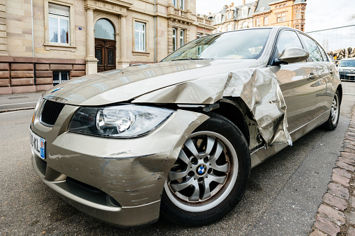 Strasbourg, France - Mar 12, 2019: Detail of luxury BMW german car parked on city street with damaged front by accident on the road