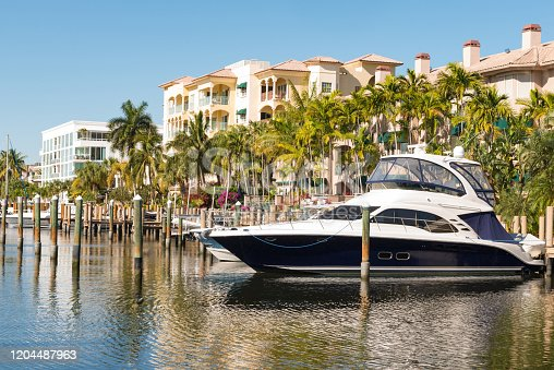 This is a photograph of a luxury boat docked in canal waters behind a residential building surrounded with palm trees by Las Olas in Fort Lauderdale, Florida.