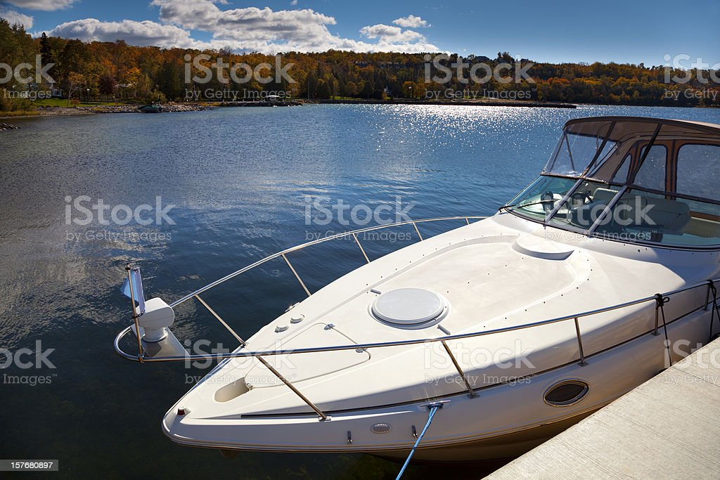 Luxury Boat Moored in Sunny Autumn Harbor stock photo