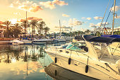 Yacht marina in Cala d'Or on the island of Mallorca in Spain. Moored boats illuminate the rays of the rising sun.