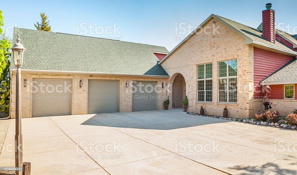 Luxury Brick Home With Three Stall Garage and Vast Driveway stock photo