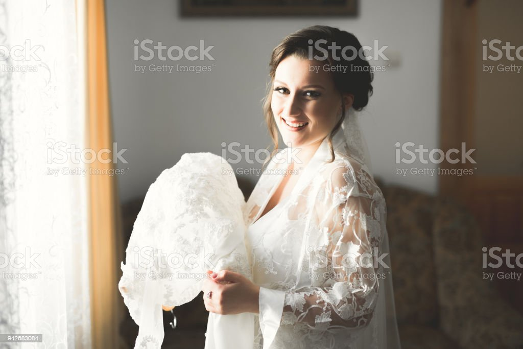 Luxury bride in white dress posing while preparing for the wedding ceremony stock photo