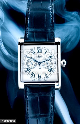 Leiden, The Netherlands - September 3, 2008: Product shot of a Cartier Tank Mono Poussoir Collection Privee wristwatch on black background with smoke effects. This watch has a white gold case and an black alligator leather strap. Only one hundred watches were produced, which makes it very exclusive.