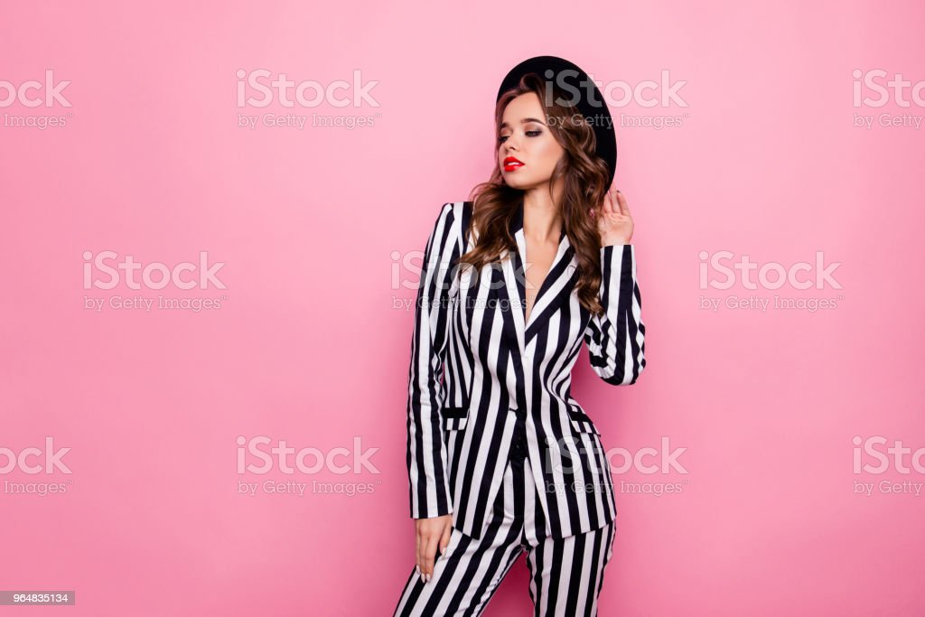 Luxury, charming stylist in hat with modern hairdo, in jacket, pants is ready for black and white party, going for event, posing over pink background royalty-free stock photo