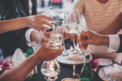 Luxury christmas celebration. People hands toasting with champagne glasses at delicious feast outdoors in the evening. Family and friends clinking glasses and cheering with alcohol
