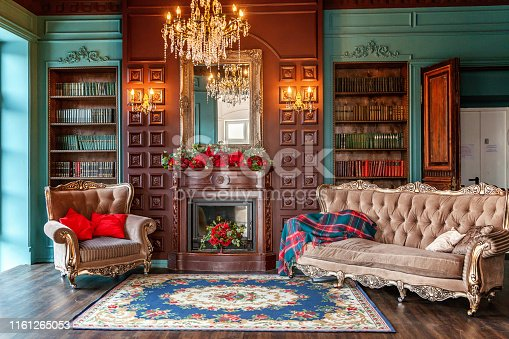 istock Luxury classic interior of home library. Sitting room with bookshelf, books, arm chair, sofa and fireplace 1161265053