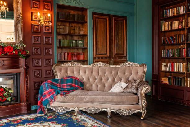 intérieur classique de luxe de la bibliothèque à la maison. salle d'assise avec bibliothèque, livres, fauteuil, sofa et cheminée - style victorien photos et images de collection