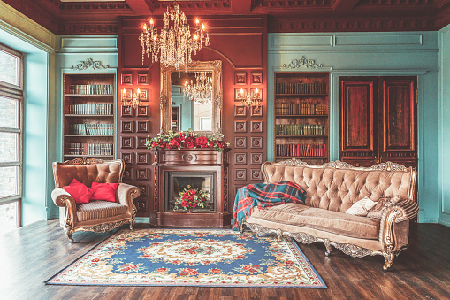 istock Luxury classic interior of home library. Sitting room with bookshelf, books, arm chair, sofa and fireplace 1190631809