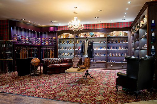 Interior of a high-quality clothing shop for men with shoes, belts and accessories on display. Chandelier with leather chairs creating a cosy luxurious atmosphere.