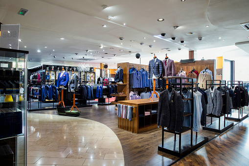 Interior of a high-quality clothing shop for men with many suits and neckties on display