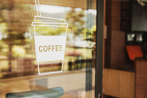 Luxury coffee shop sign on the glass door. For art texture or web design backgrund.
