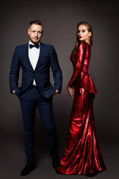 Luxury Couple, Beautiful Fashion Woman in Red Dress, Elegant Man in Suit Tuxedo stock photo