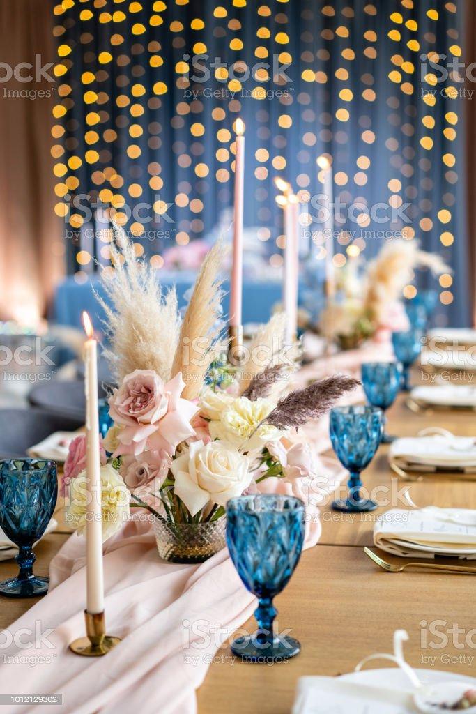 Luxus-Dinner im Restaurant Bankett. Wunderschöne und exquisite Dekoration der Hochzeitsfeier. Bankett serviert Tisch mit einer Beige rosa Tischdecke, Teller und Leuchter mit Kerzen. – Foto