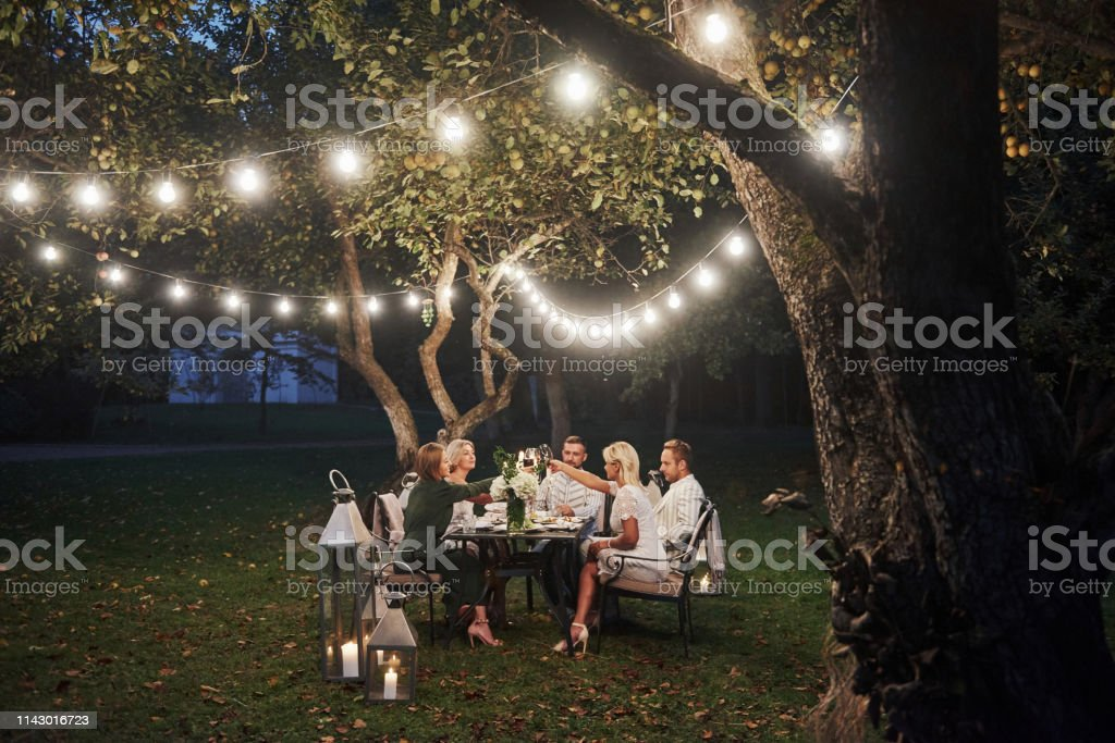 Luxury dinner. Evening time. Friends have a dinner in the gorgeous...