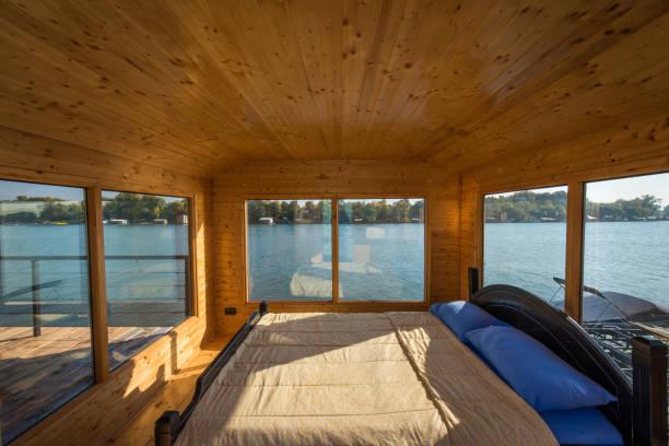 luxus doppelbett aus holz schlafzimmer fluss mit großen fenstern - bett landhausstil stock-fotos und bilder