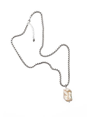Luxury elegant baroque pearl pendant with silver chain isolated on white background. Close-up shot