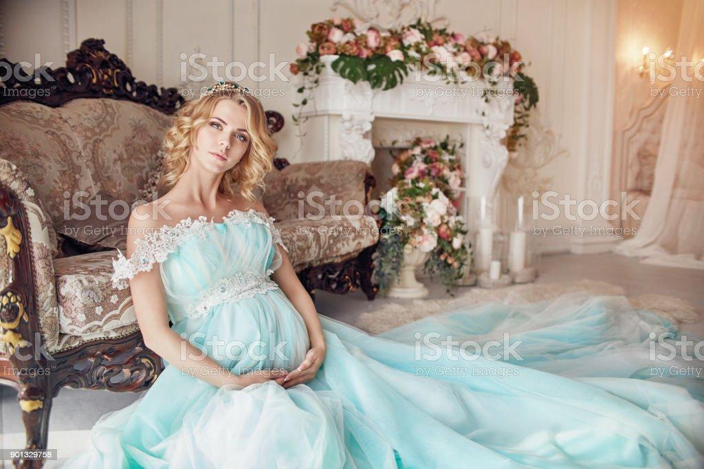 Luxe mode blonde femme enceinte dans une robe de mariée. Femme enceinte de mariage. Jeune fille attend la naissance d'un enfant. Élégante robe cher de couleur bleu azur. Femme enceinte et son bébé dans le ventre - Photo