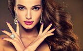 Beautiful model brunette with long curled hair. Luxury fashion style, nails manicure, cosmetics, make-up and brilliant jewelry.