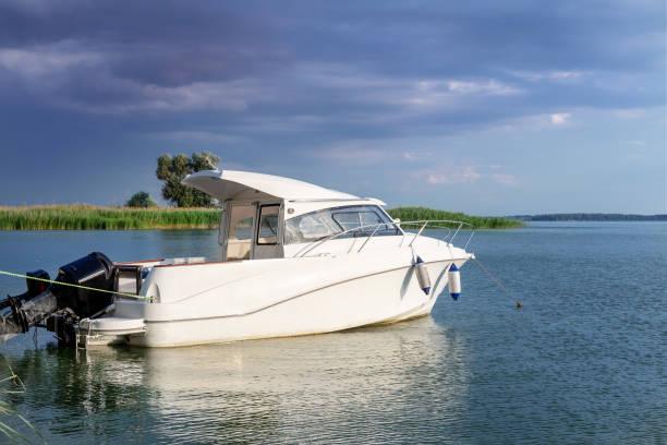 luxe motor vissersboot afgemeerd aan de kust in de baai aan de rivier- of meerwater. donkere stormy sky met donder wolken op de achtergrond. reizen en recreatie, slechte weersvoorspelling - aangemeerd stockfoto's en -beelden