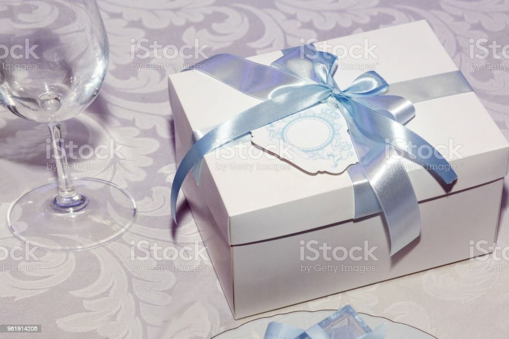 luxury gift box with blue ribbon on decorated tables at rich wedding reception. stylish arrangements. expensive catering. space for text. present for wedding couple. christmas gift stock photo