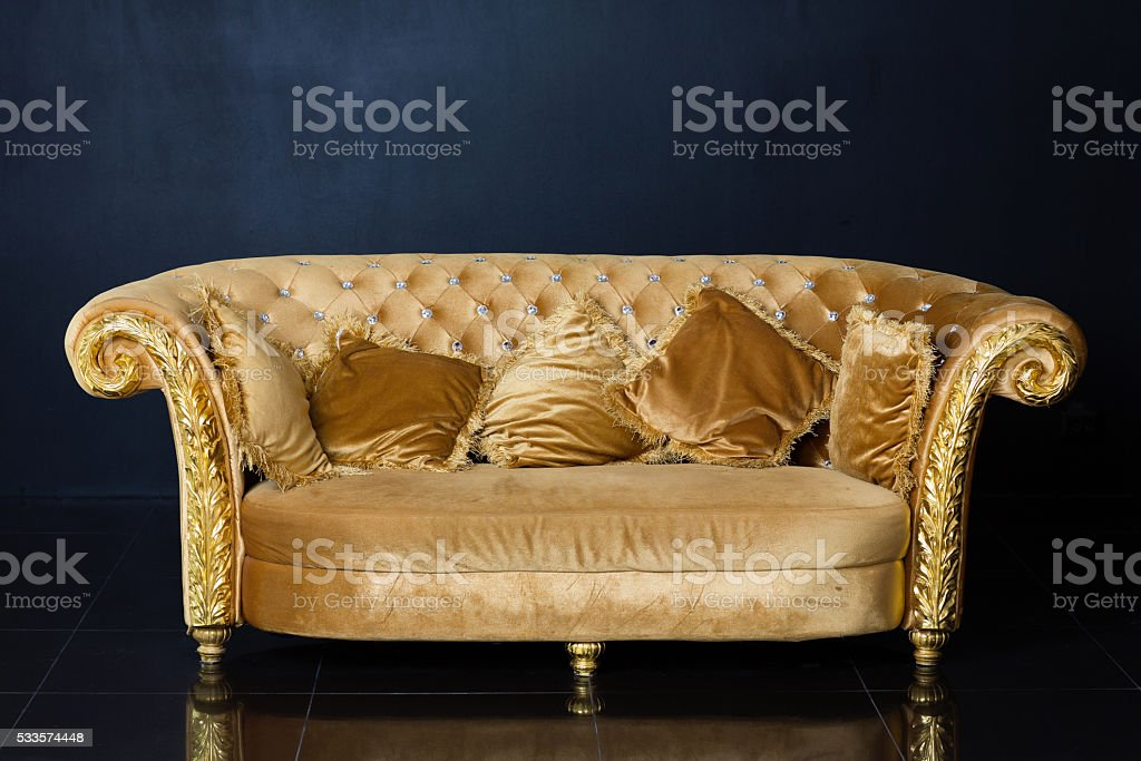 Luxury golden sofa on a black background stock photo