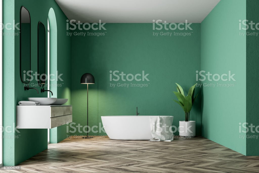 Minimalistic green bathroom interior with a white bathtub, a towel...