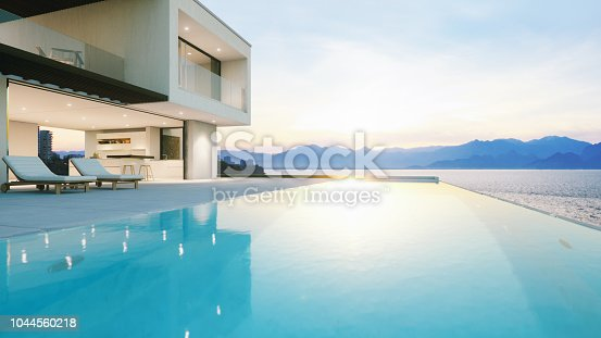 Modern luxury house with infinity pool over the ocean at sunset.
