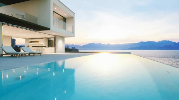 luksusowa willa wakacyjna z basenem bez krawędzi o zachodzie słońca - luksus zdjęcia i obrazy z banku zdjęć