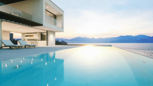 Luxury Holiday Villa With Infinity Pool At Sunset Modern luxury house with infinity pool over the ocean at sunset. holiday villa stock pictures, royalty-free photos & images