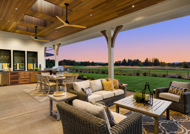 Luxury home exterior at sunset: Outdoor covered patio with kitchen, barbecue, dining table, and seating area, overlooking grass field and trees. stock photo