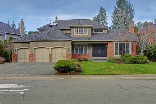 Luxury home exterior with three car garage. stock photo