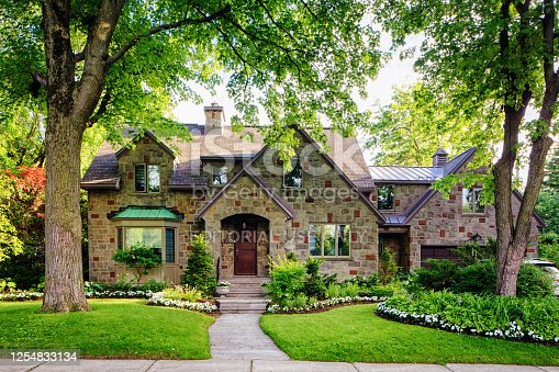 Luxury house in Town of Mount Royal on a sunny Summer evening, with gorgeous front flowerbeds and a nice modern extension. TMR is known for its luxury homes and is a green city, promoting gardens, parks and green spaces.